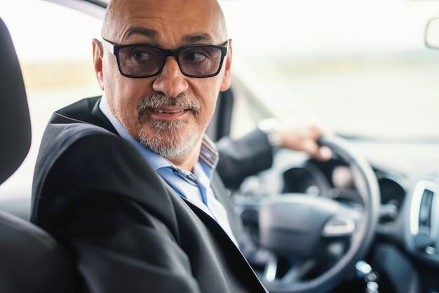 ひげを生やしたシニア大人が後退するために運転しています。後部座席から撮影した写真。