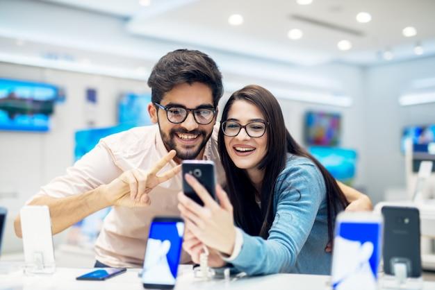 Молодые довольные стильной очаровательной парой обнимаются, тестируя новую модель мобильного телефона со стола в техническом магазине.