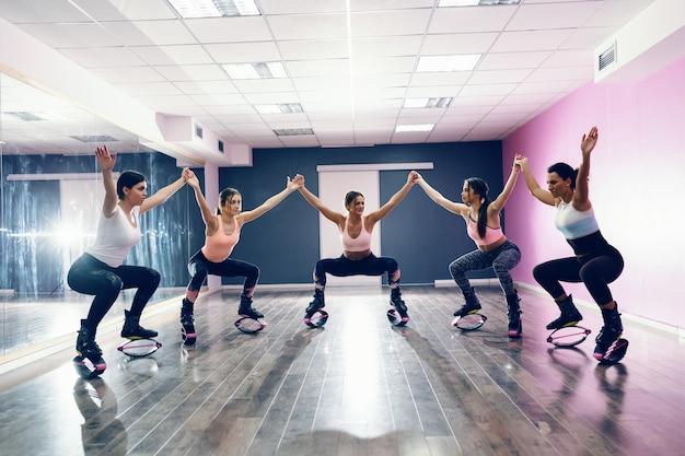 手を繋いでいて、カングーでスクワット持久力をしている女性の小さなグループは、靴をジャンプします。フィットネススタジオのインテリア。
