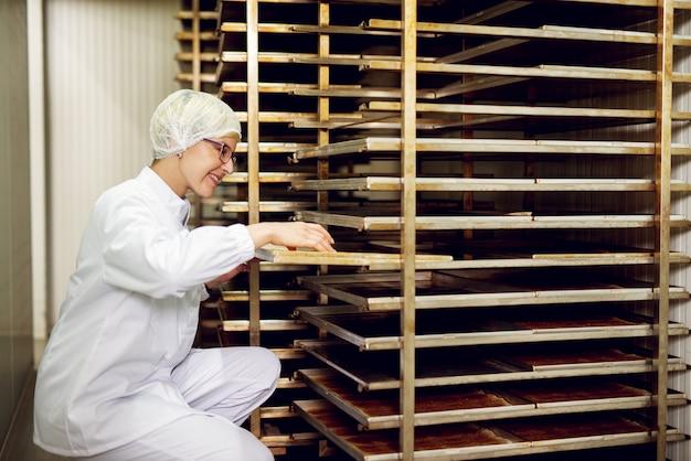 Молодой жизнерадостный женский работник в стерильной ткани рассматривая свеже испеченные печенья на полке печенья в комнате хранения хлебопекарни.
