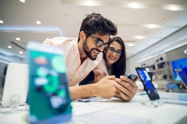ハイテクストアで新しい携帯電話を選択する陽気な魅力的な幸せな若い学生愛のカップルのフォーカスビューを閉じます。