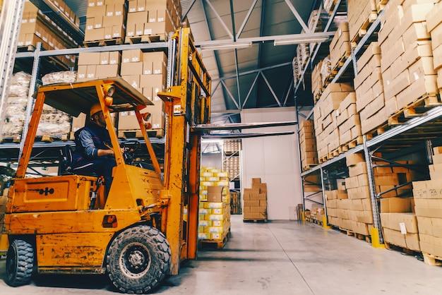 男は倉庫でフォークリフトを運転します。棚や箱の周り。