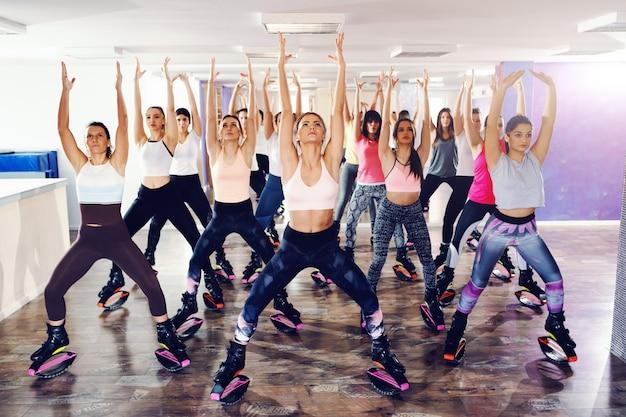 カングーでエクササイズを行うスポーツウェアの女性のグループは、フィットネススタジオでフットウェアをジャンプします。