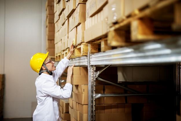 工場の保管エリアにあるパレット上の茶色のボックスのスタックでステッカーのメモを読んで若いうれしそうな女性労働者。