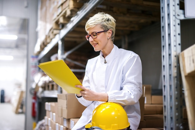 ボックスの上に座って、書類の手フォルダーに保持している女性労働者。倉庫のインテリア。