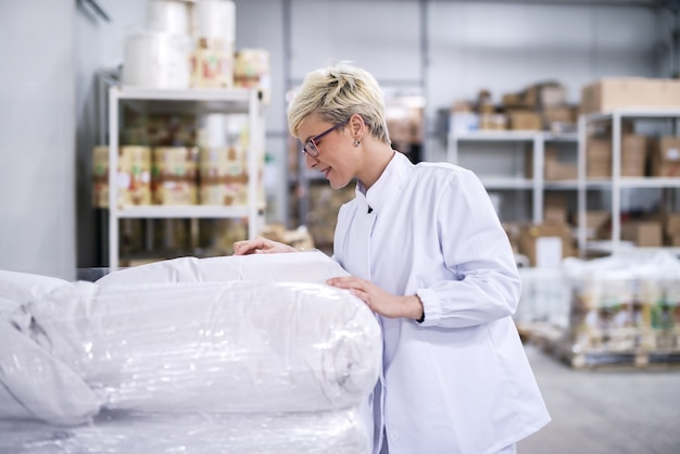 小麦粉の袋に食材を読んで女性工場労働者。倉庫のインテリア。