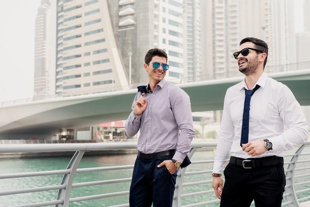 ドバイマリンで歩くと新しいビジネスステップについて話しているスーツで若い成功した実業家。