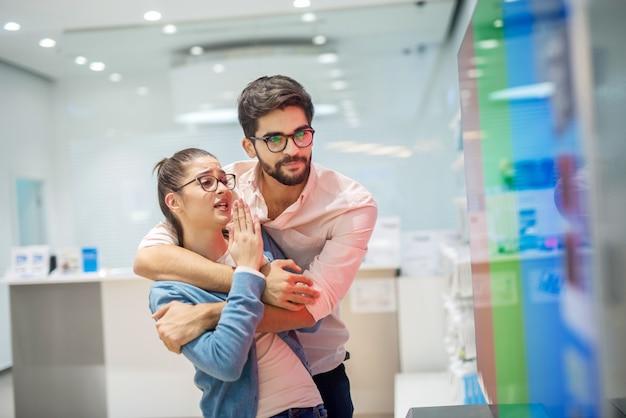 Молодая веселая пара в электронном магазине. девушка убеждает своего парня своим новым телевизором для своего дома.