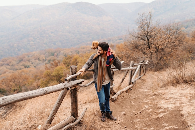 Красивый человек смешанной гонки полагаясь на загородке и держа его пуделя абрикоса на плече пока смотрящ красивый вид. на заднем плане леса и горы, время осени.