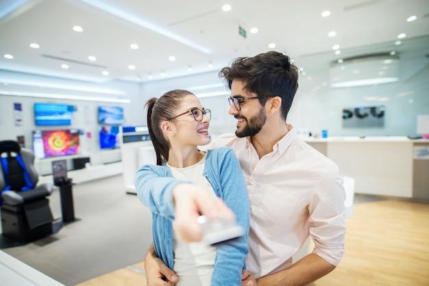Молодая счастливая пара ищет телевизор в электронный берег. девушка держит пульт дистанционного управления и глядя на своего парня.