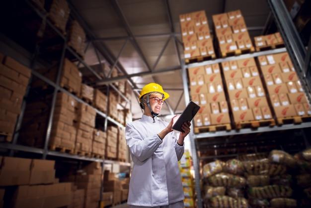 若い陽気な女性労働者はタブレットを使用して、工場の貨物エリアで滅菌布と黄色いヘルメットを着用しながら笑顔します。