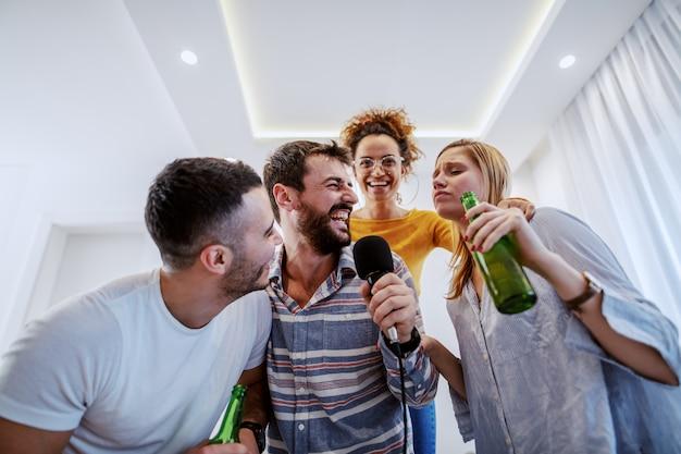 Группа в составе друзья имея вечеринку караоке дома. мужчина держит микрофон, в то время как другие держат пиво.