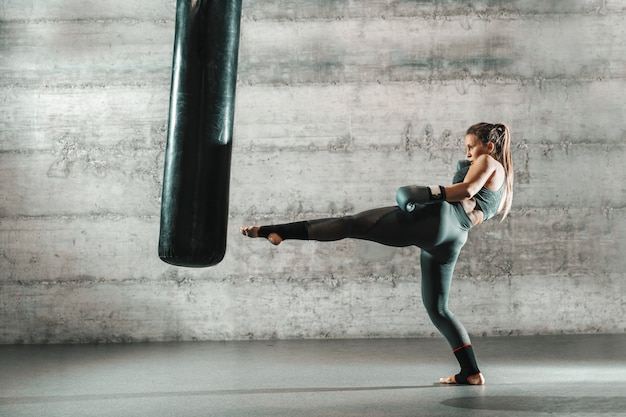 Кавказская женщина в спортивной одежде и с боксерские перчатки ногами сумку в тренажерном зале.