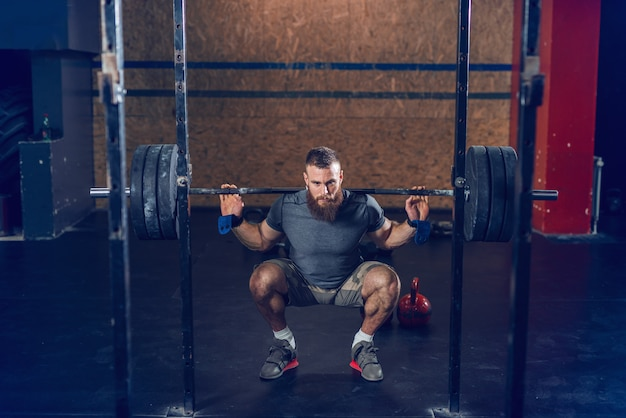 しゃがんだ姿勢でバーベルを持ち上げるスポーツウェアの筋肉集中ヒップスター。