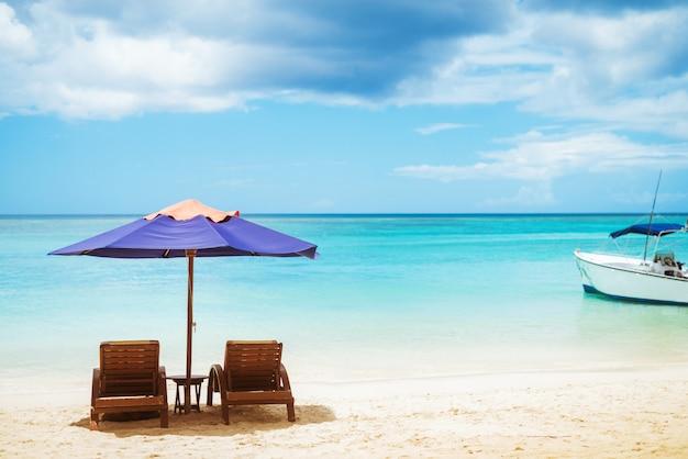 Удивительный вид на мирное побережье с двумя деревянными шезлонгами с красочным зонтиком и белой яхтой