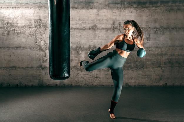 ポニーテール、スポーツウェア、裸足、ジムで袋を蹴るボクシンググローブを備えた力強いブルネット。