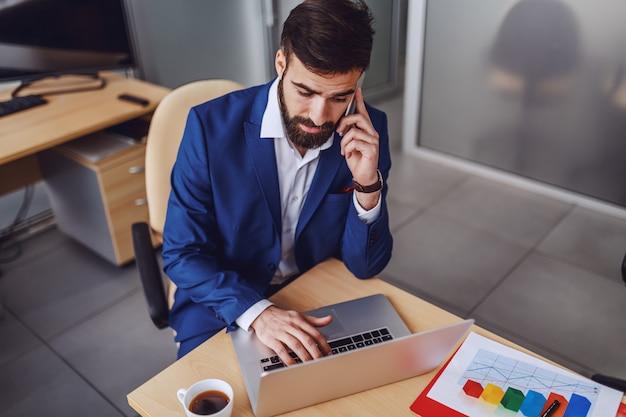 若い焦点を絞った魅力的なひげを生やした首長がオフィスに座って、ラップトップで入力して、クライアントとのビジネスコールを持っています。
