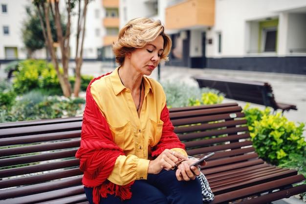 公園のベンチに座っている金髪の短い髪のゴージャスな白人おしゃれな年配の女性