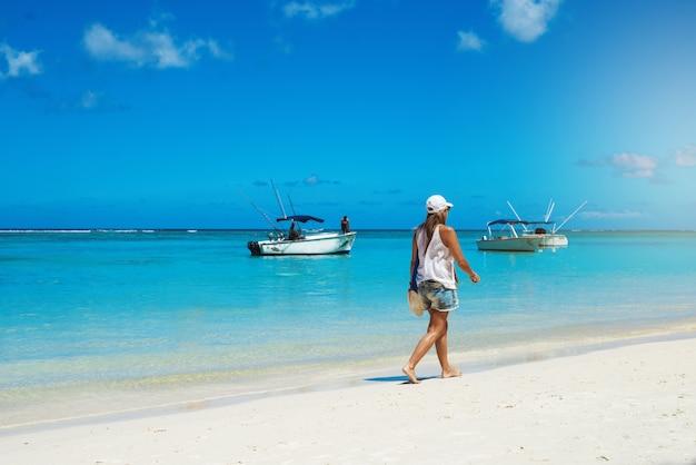 Летний отпуск. загорелая женщина прогуливается по берегу, наслаждаясь беззаботным временем