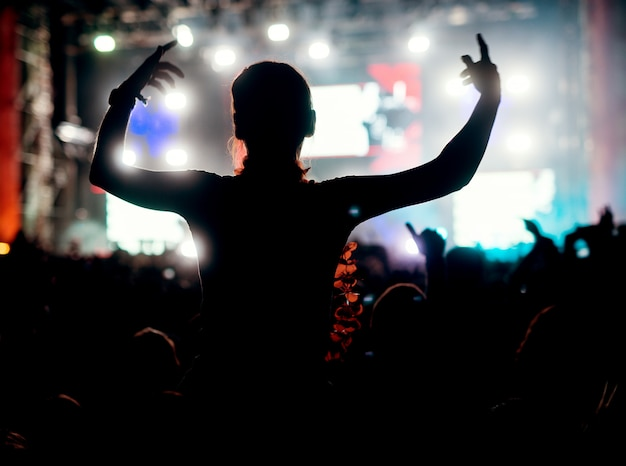 彼女の好きなバンドの人々を楽しむ女の子は音楽祭を群衆します。