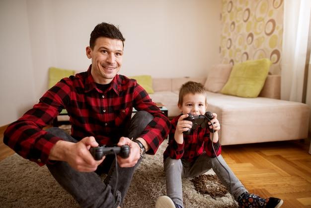 Молодой веселый возбужденный отец и сын в одной красной рубашке играют в консольные игры с геймпадами в светлой гостиной.