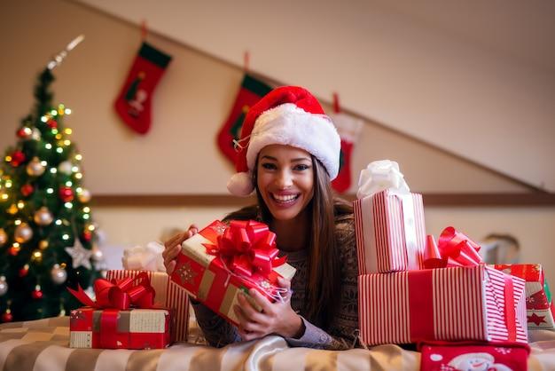 Милая веселая молодая девушка с шляпой санты лежит на кровати с подарком в руках