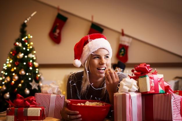 プレゼントと悪い上に横たわるクリスマス休暇のためのポップコーンを持つ豪華な若い女の子。