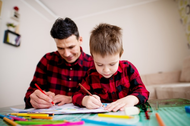 Молодой сфокусированный отец и сын в такой же красной картине рубашки с красочным комплектом карандашей пока сидящ на таблице в яркой живущей комнате.