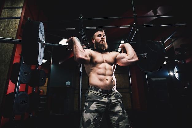重いバーベルを保持している強力なやる気のボディービルダー上半身裸の男