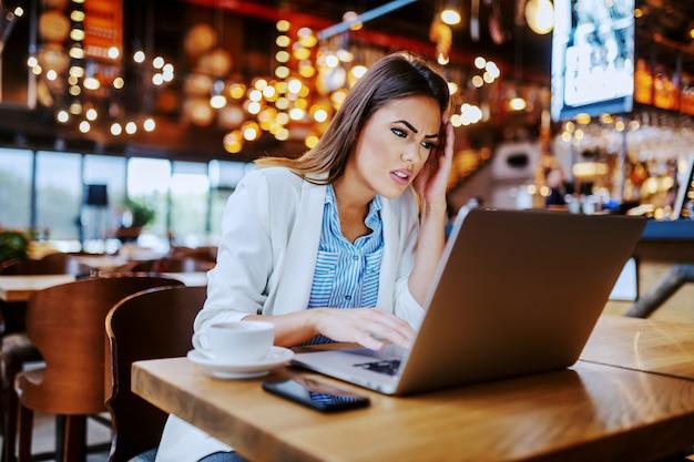 Привлекательная нервная кавказская коммерсантка сидя в кафе и используя компьтер-книжку