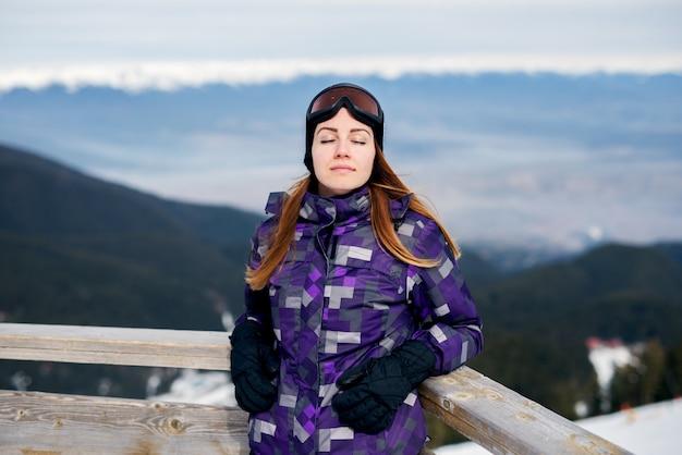 Крупным планом молодая красивая девушка, стоя возле забора в зимней одежде с закрытыми глазами.