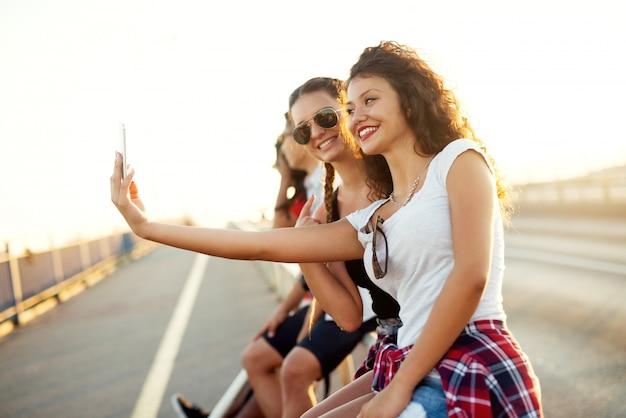 Молодые красивые девушки, принимая селфи на улице.