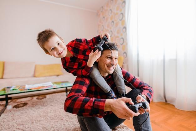 День отца и сына. веселый отец и сын, играя в видеоигры. сын сидит на плечах отца.