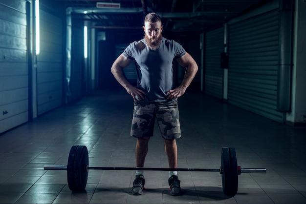 強力なスポーティなボディービルダーが重い物を持ち上げる準備をしている写真。
