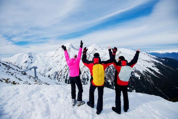 山の頂上に冬服を着て眺めを楽しむ人々の背面図。