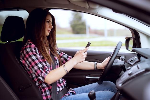 Молодая беззаботная милая девушка текстовых сообщений и вождение одновременно.