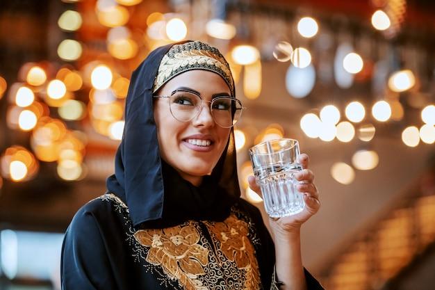 Великолепная позитивная мусульманка в традиционной одежде с красивой улыбкой сидит в кафе