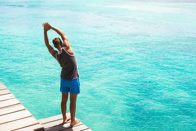 美しいビーチで朝の体操をしている男の背面図