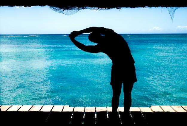 海でストレッチ体操をしている若いハンサムな男。夏の朝の美しい景色。