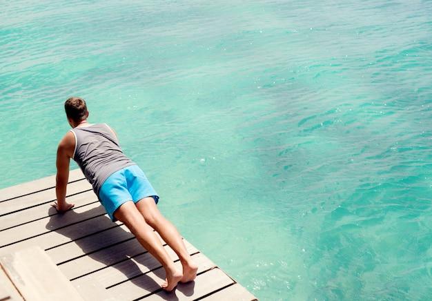 夏の屋外トレーニングを行う若い男。美しいターコイズブルーの海のそばで腕立て伏せをしています。