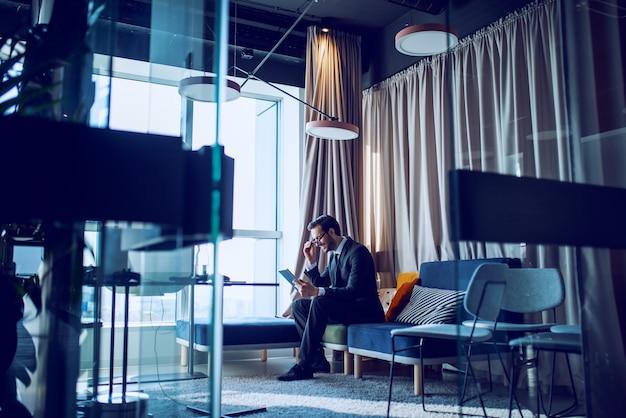 魅力的でエレガントな笑みを浮かべて白人ひげを生やしたビジネスマンのスーツと彼のオフィスのソファーに座っているとタブレットを使用して眼鏡。