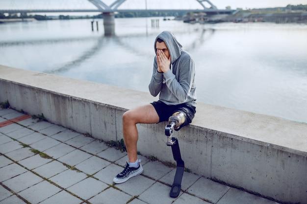 健康な白人の障害を持つスポーツマンを、人工の脚と、岸壁に座って休んでいる頭にパーカーを合わせます。