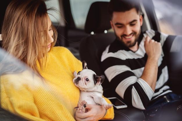 Довольно улыбающаяся современная девушка в желтом свитере держит маленькую милую собачку, сидя в машине с красивым бородатым парнем.