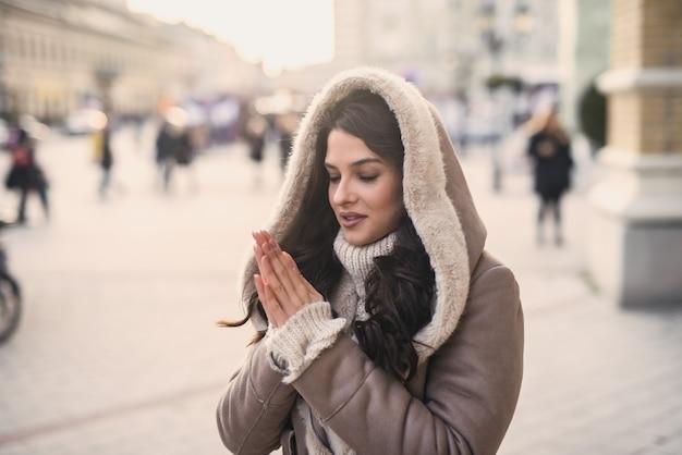 寒い天候下で路上に立っている間手を温める若い女性。