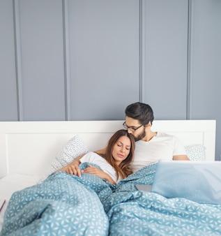 Улыбающийся кавказский бородатый мужчина в очках с помощью ноутбука и целует в голову свою любящую жену. утреннее время.