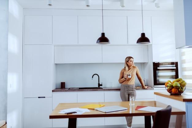 魅力的な白人金髪のファッショナブルな女性がキッチンのカウンターにもたれて、マグカップを押しながらコーヒーを飲みながらトラフウィンドウを探しています。