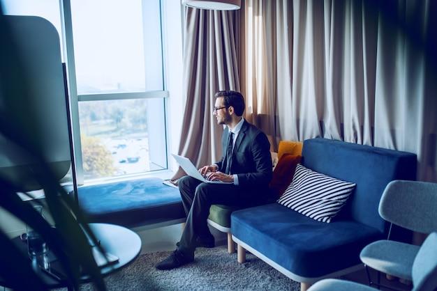 ハンサムな白人のひげを生やしたビジネスマンのスーツと眼鏡のソファの上のオフィスに座って、ラップトップを膝の上に持って、トラフウィンドウを探して、考えています。