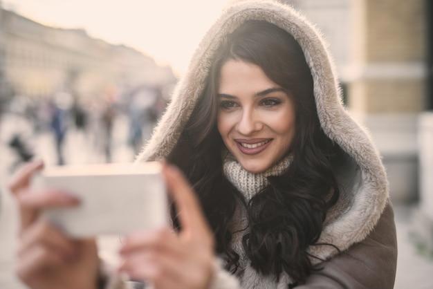 通りに立っている間タブレットを使用して女性のクローズアップ。女性と技術の屋外コンセプト。