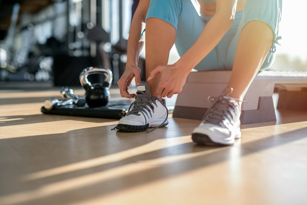 ジムでトレーニングする前に靴ひもを結ぶ女性の手のクローズアップ。