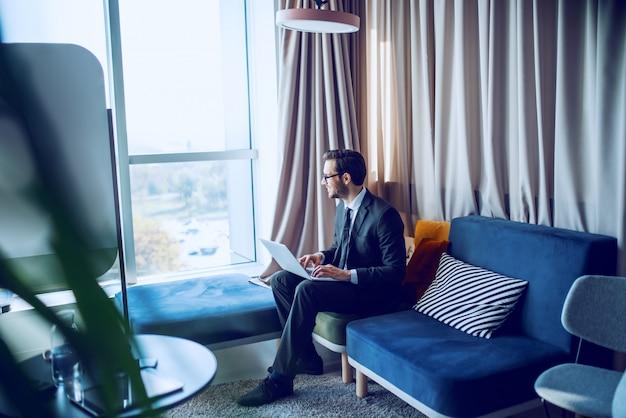 ハンサムな白人のひげを生やしたビジネスマンのスーツと眼鏡のソファの上のオフィスに座って、ラップトップを膝の上に持って、トラフウィンドウを探して、笑顔で。